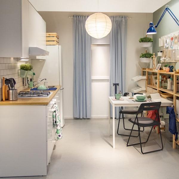 Kuchynská zostava Knoxhult v bielej farbe s množstvom úložného priestoru a spotrebičov.