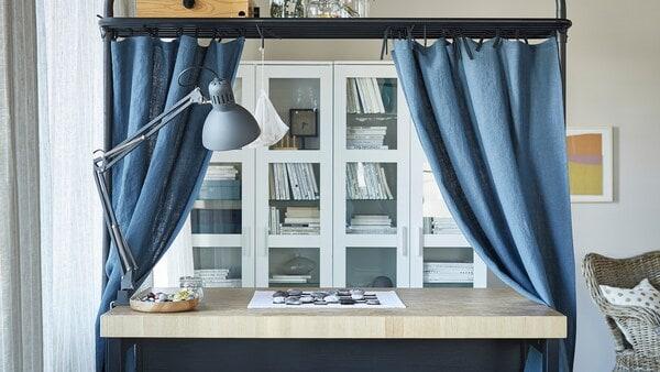 Kuchynský ostrov v obývacej izbe využitý ako úložný priestor s vrchným rámom a modrými závesmi.