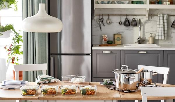 Kuchynský stôl s pripraveným jedlom rozdeleným na porcie v sklenených nádobách.