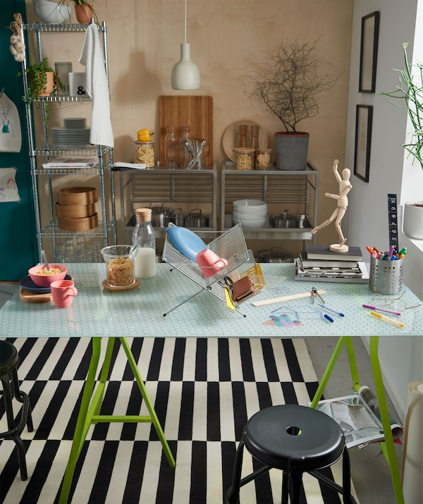 Kuchynský stôl so sklenenou stolovou doskou a stojanom na riad, ktorý oddeľuje miesto na jedenie a kreatívne aktivity.
