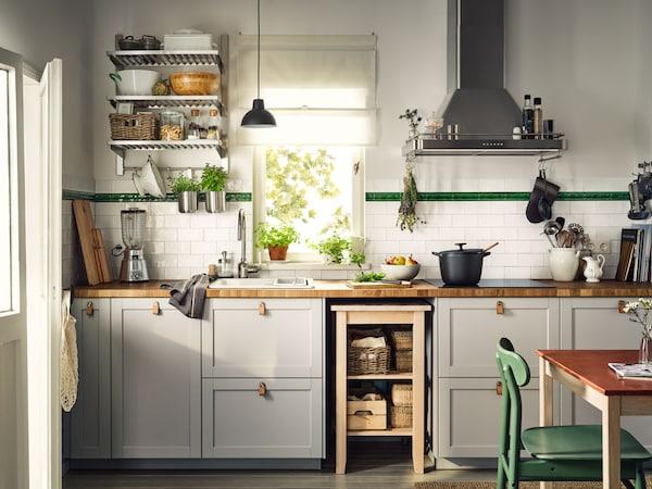 Küche mit hellen Fronten und einem Tisch mit grünem Stuhl.