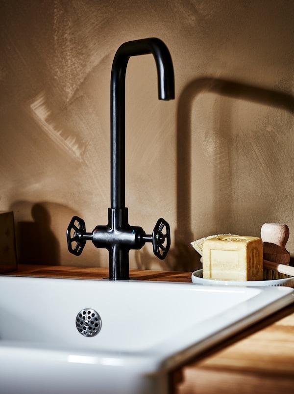 Küchenspüle mit der GAMLESJÖN Zweigriff-Mischbatterie in einer Mischung aus Tradition und Moderne, dazu Spülutensilien.