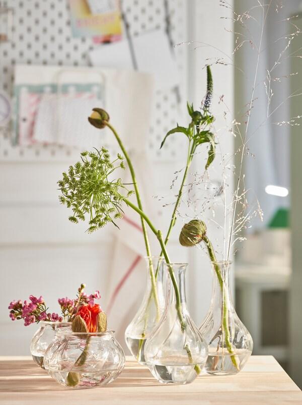 Különböző magasságú VILJESTARK üvegvázákban egy-egy szál virág vagy növény, egy fa konyhapulton.