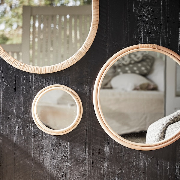 Különböző méretű, rattan keretes kerek tükröket látunk  egy söté fa felületen, tekintetet vonzó elrendezésben.