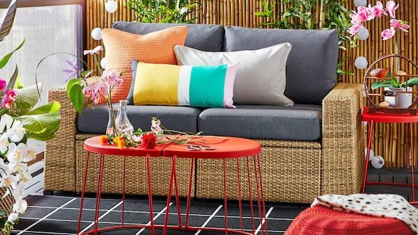 Kültéren berendezett ülősarok fotellel, piros asztallal, színes párnákkal és növényekkel.