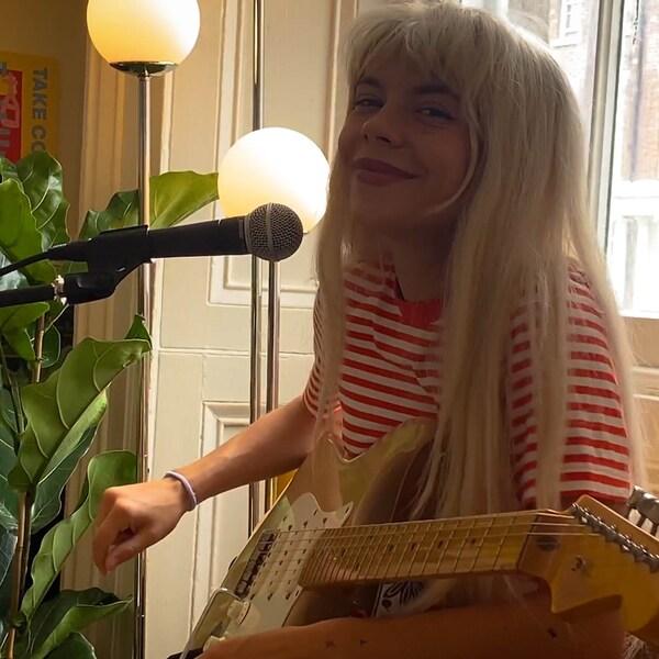 Künstlerin Pixey sitzt Zuhause mit einer Gitarre in der Hand, sie trägt ein rotweiss gestreiftes Shirt