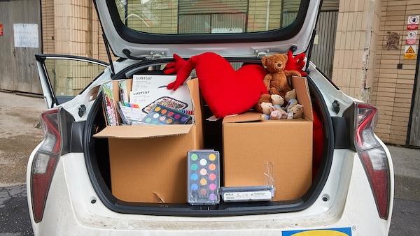 Kufor auta plný hračiek a potrieb na kreslenie pre deti.