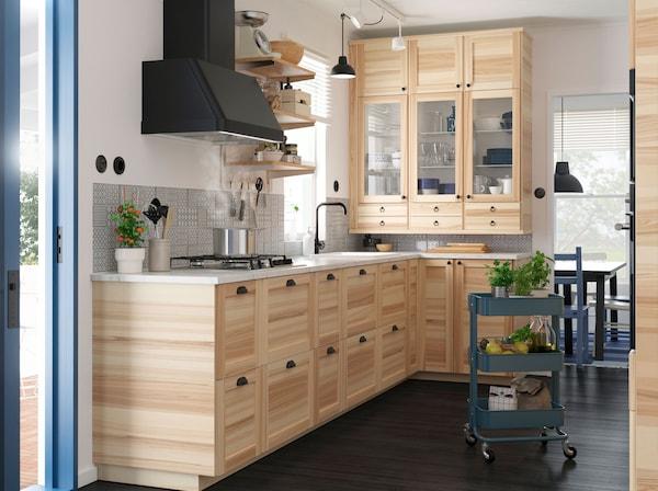 Kuhinja s IKEA TORHAMN pokrivnim pločama od punog jasena, ladicama i vratima zidnih elemenata, crnom napom i plavim RÅGSKOG kolicima.