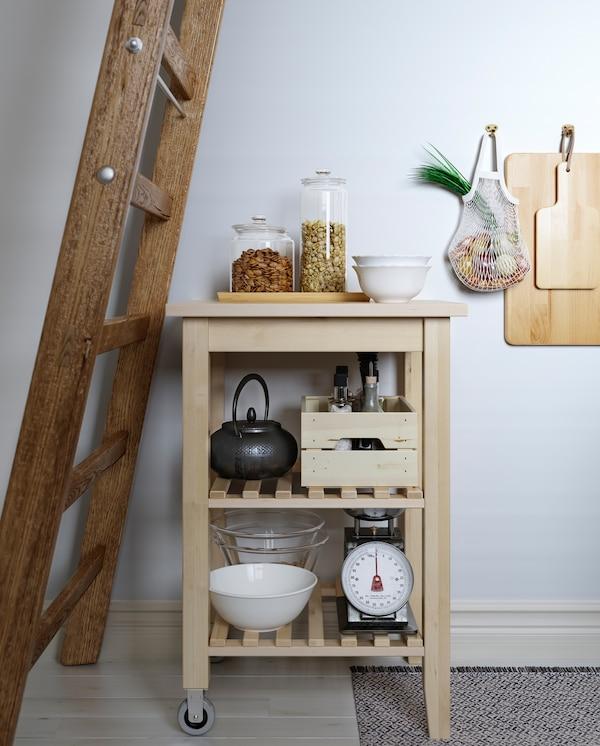 Kuhinjska kolica od brezovine nalaze se ispod drvenih merdevina. Kuhinjski pribor, tegle i čajnik su na policama u kolicima.