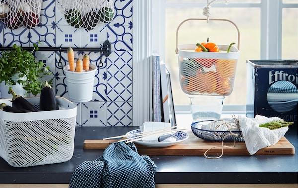 Kuhinjska radna površina s različitim prehrambenim proizvodima u visećim i stojećim spremnicima, kao što su KUNGSFORS mrežaste vreće i RISATORP košare.