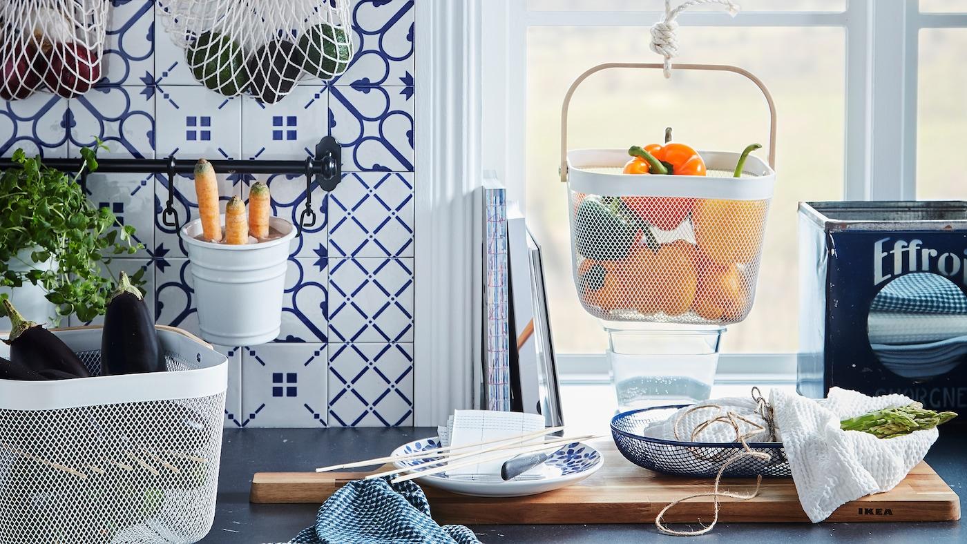 Kuhinjski pult z razno zelenjavo v visečih in stoječih vsebnikih, na primer v KUNGSFORS mrežah in RISATORP košarah.