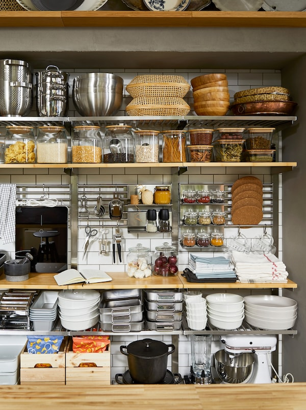 Kuhinjski zid s ostavom i otvorenim prostorom za odlaganje, s KUNGSFORS policama, punim suvih namirnica u teglama i dodacima za kuvanje.