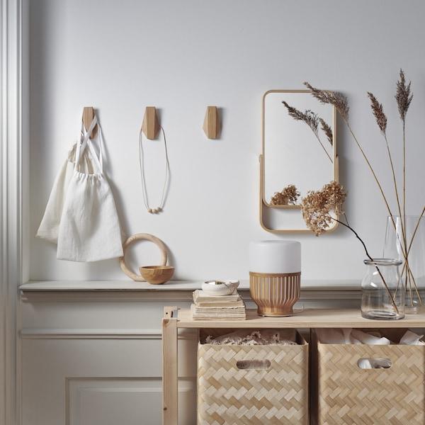 Kuke od bambusa i ogledalo na zidu iznad drvene jedinice za odlaganje s kutijama od bambusa.