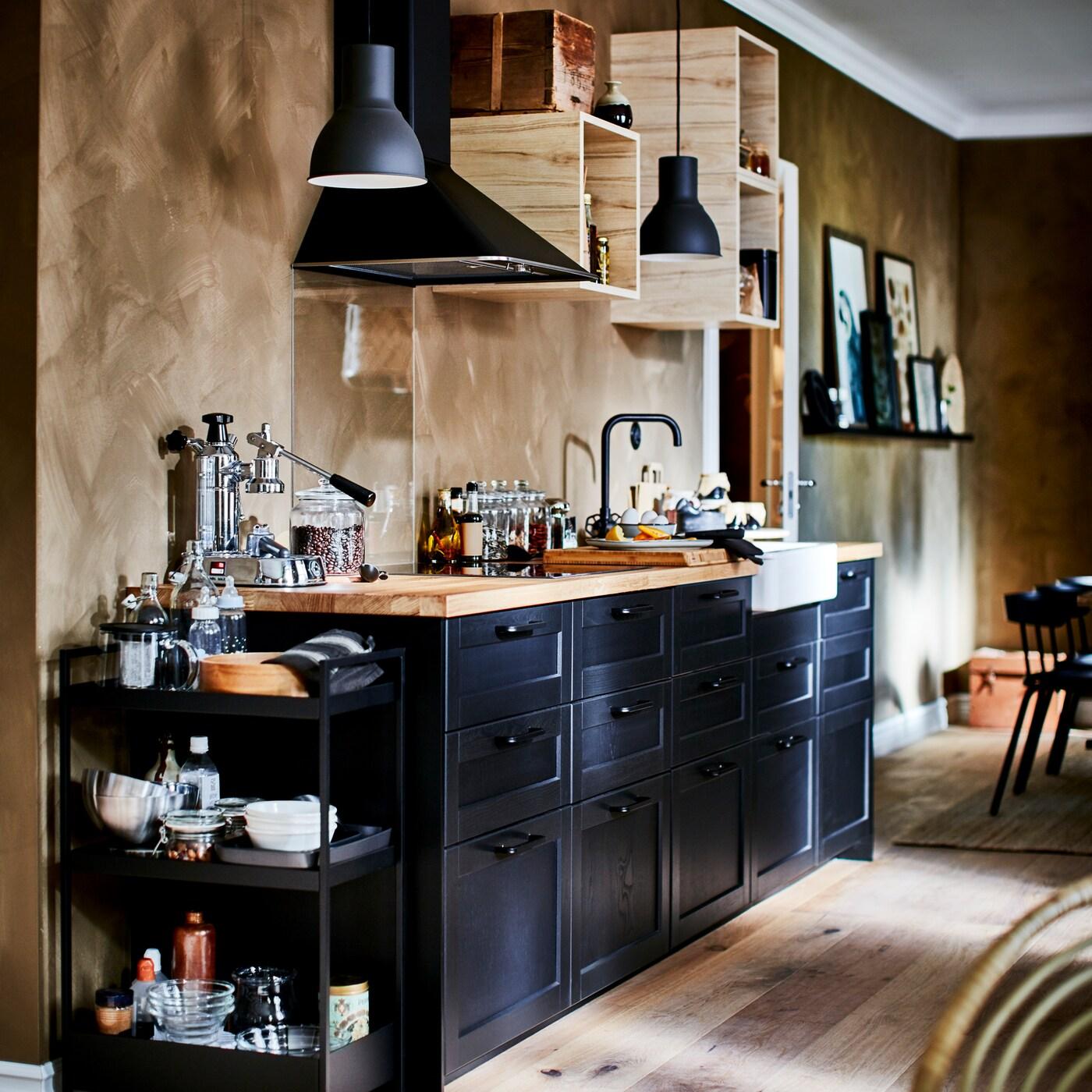 Кухня с черными фронтальными панелями для ящиков, деревянной столешницей, черной тележкой, открытыми настенными шкафами и двумя темно-серыми подвесными светильниками.
