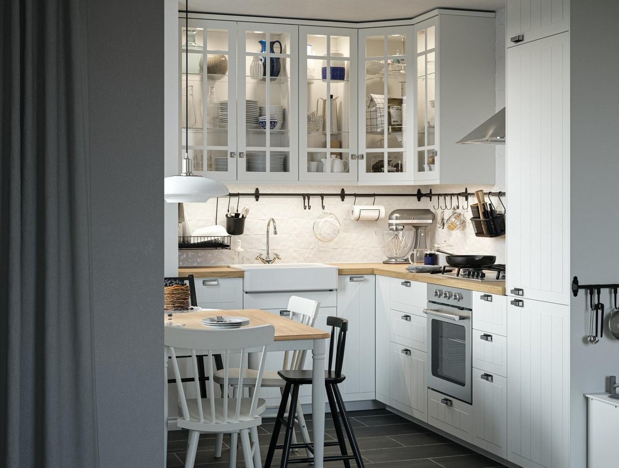 Кухня в традиционном стиле: белые фронтальные панели и шкафы со стеклянными дверцами, обеденный стол, стулья и детская кухня.