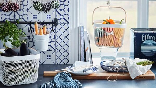 Кухонна стільниця з різними продуктами, що зберігаються у підвісних і звичайних кошиках на кшталт KUNGSFORS КУНГСФОРС сіток та RISATORP РІСАТОРП кошиків.