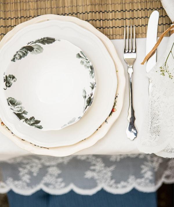 Kukkakuvioinen lautanen ja koristereunainen lautanen muodostavat kauniin parin. Kuvassa myös kiiltävät ruokailuvälineet ja valkoinen pöytäliina.