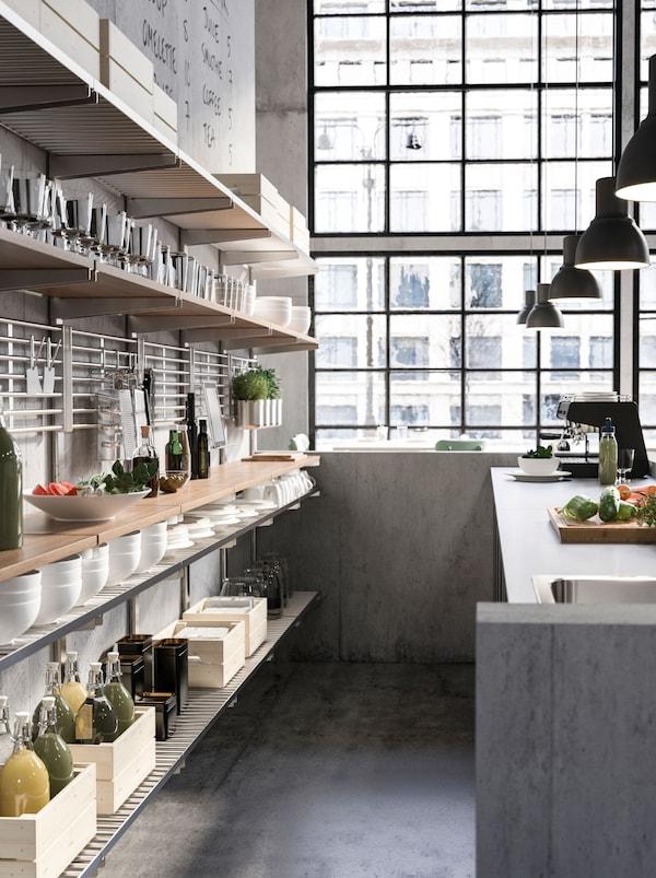 KUNGFORS-seinähyllyt kahvilatiskin takana. Avoimilla hyllyillä on kahvikannuja, kulhoja ja ruokatarvikkeita.