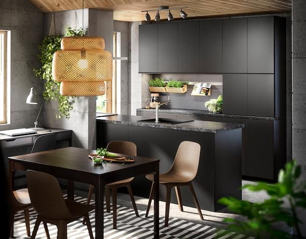 KUNGSBACKA sort køkken som et åbent køkken-alrum med spisebord med tilhørende spisebordsstole