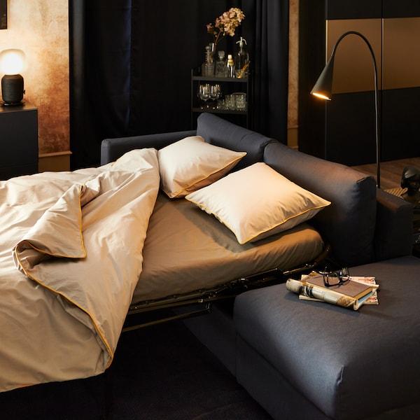 KUNGSBLOMMA jorganska navlaka i 2 jastučnice u sivoj i žutoj boji, na sofi na razvlačenje, s lampama i ormarom za izlaganje pozadi.