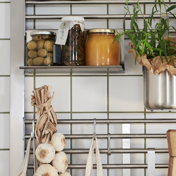 KUNGSFORS KUNGSFORS ruostumattomasta teräksestä valmistettu seinäverkko, johon on kiinnitetty purkkeja, yrttejä, valkosipulinauha ja mausteastia.