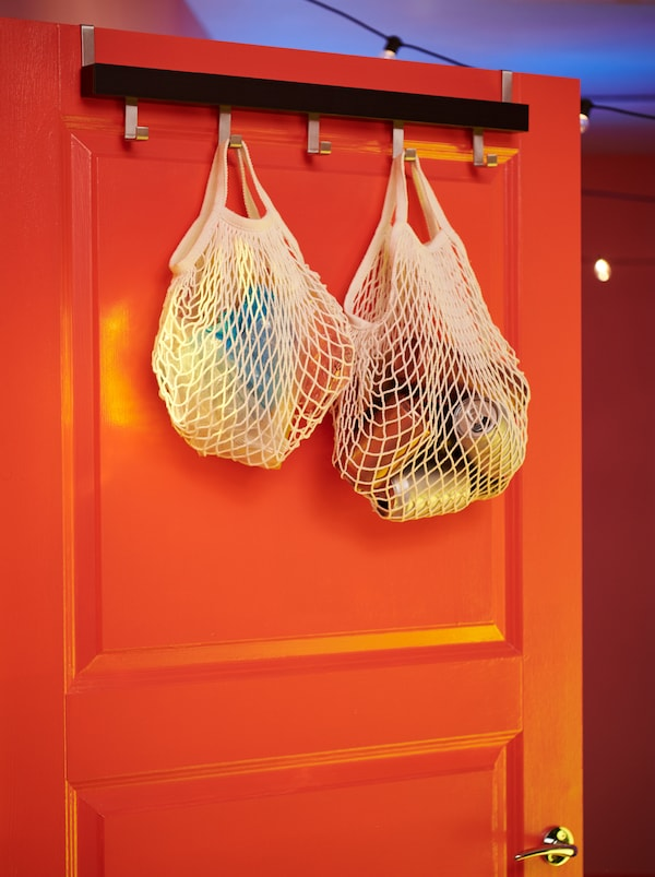 KUNGSFORS net bags filled with empty cans and similar disposables, hooked to a TJUSIG hanger at the top of a door.