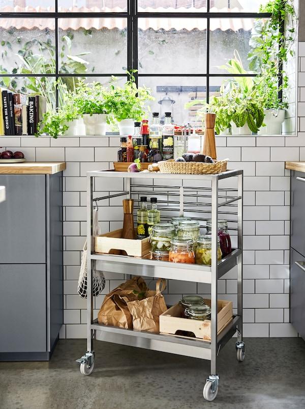 KUNGSFORS rullebord af rustfrit stål med 3 hylder og hjul, fyldt med krydderier og glas med syltede grøntsager.