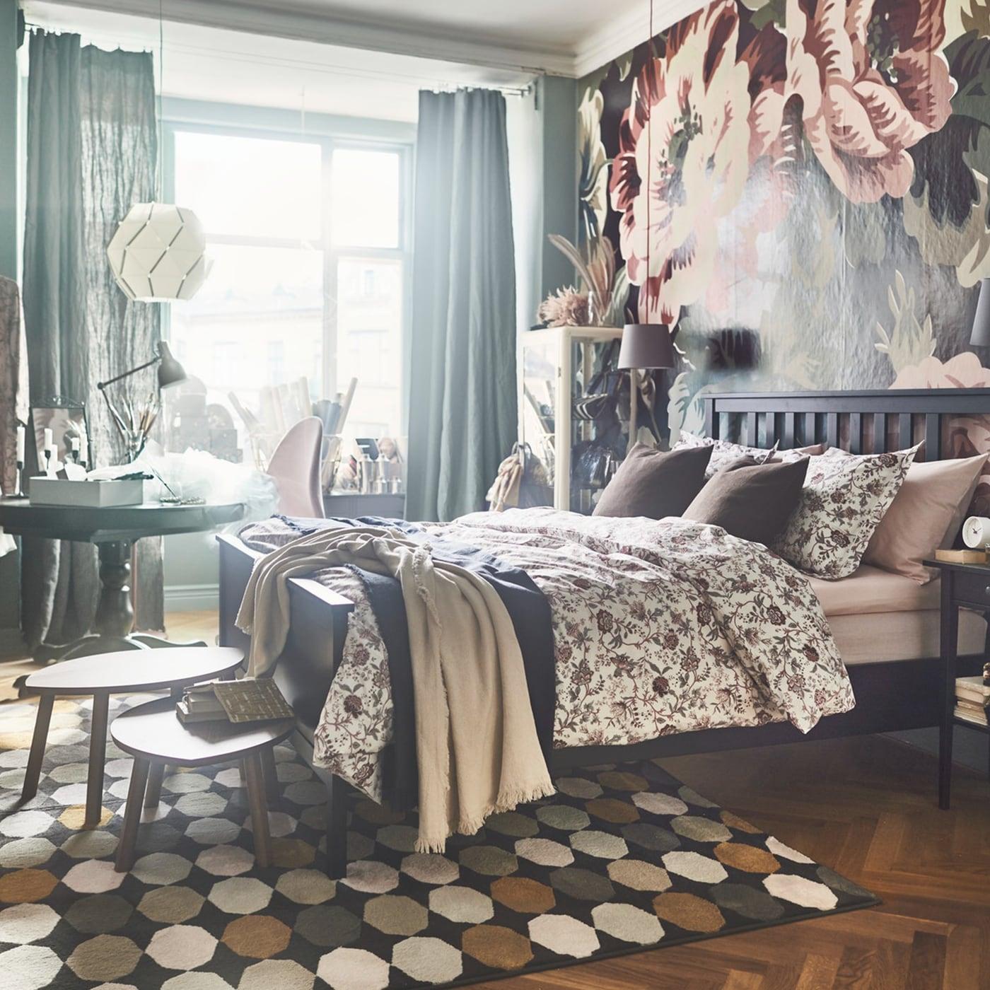 Kunterbunte Schlafzimmereinrichtung mit schwarzbraunem HEMNES Bettgestell, blumiger Bettwäsche & Tapete