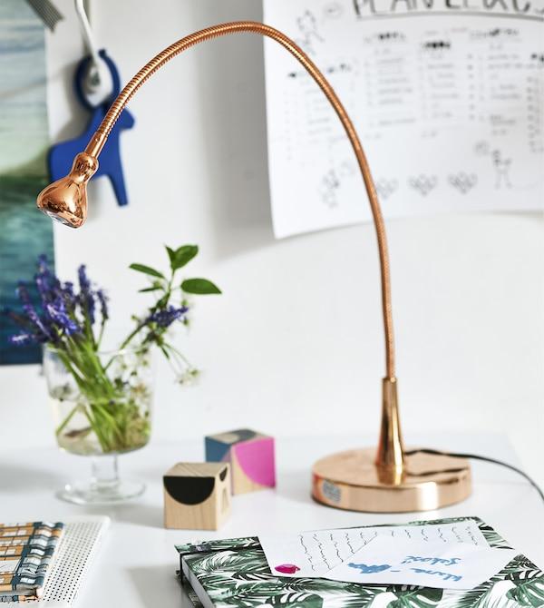 Kuparinvärinen lamppu, kukkia ja kirjoitusvälineitä kirjoituspöydän päällä.