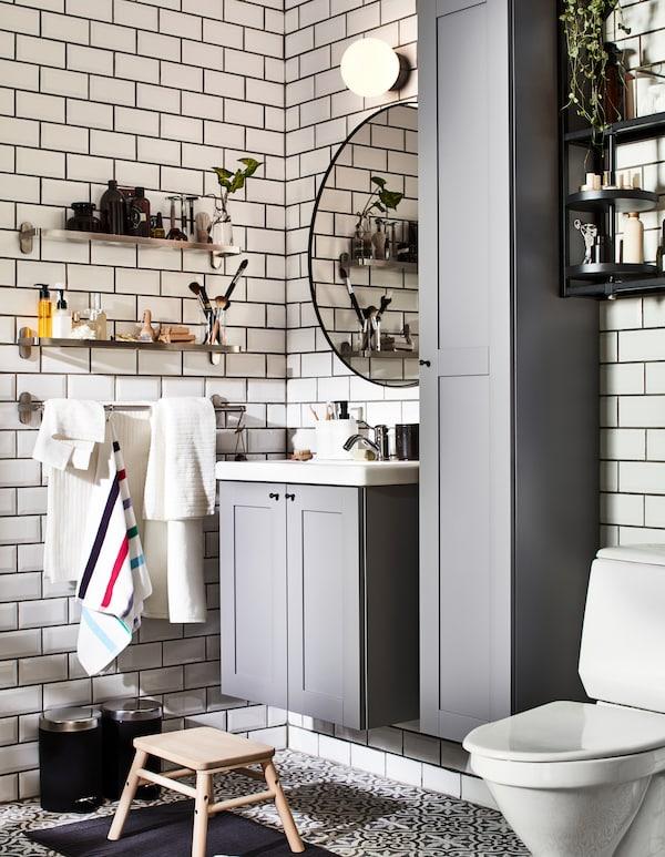 Kupatilo sa sivim ENHET kupatilskim nameštajem i zidnim BROGRUND staklenim policama, za nju i njega.