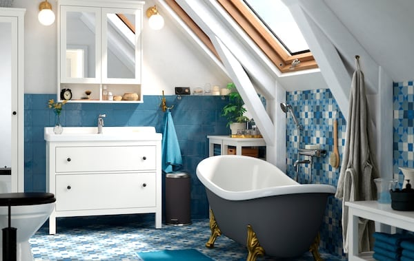 Kúpeľňa s modrou podlahou a obkladom, samostatne stojacou vaňou a bielym toaletným stolíkom so skrinkami so zrkadlami nad ním.