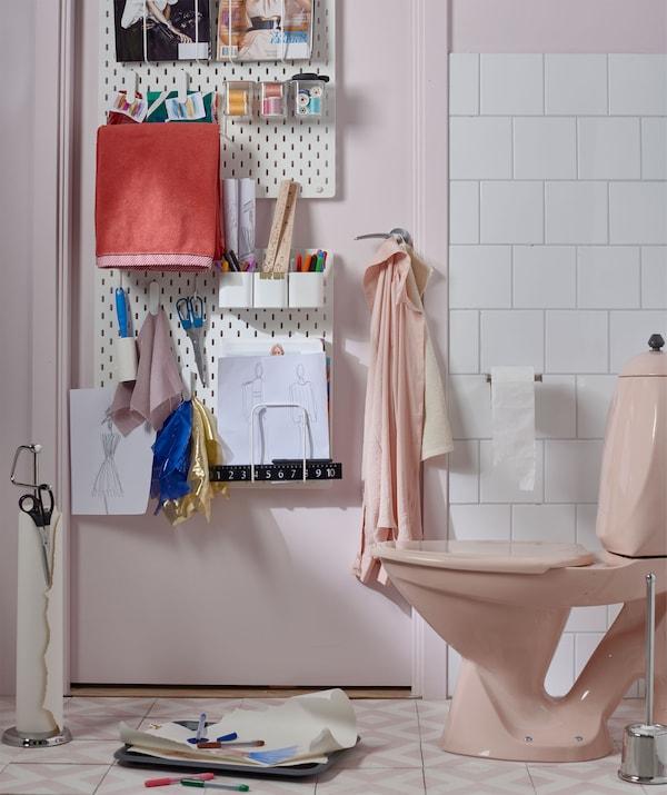 Kúpeľňa s nástenkami na dverách s perami, papierom na kreslenie a papierom a perami pri toalete.
