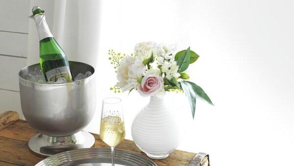 Kuplajuomaa, kuohuviinilasi ja kukkakimppu