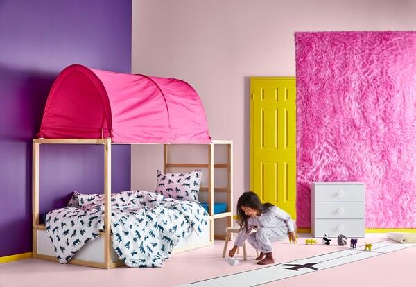 핑크 색상의 KURA 쿠라 베드텐트와 KURA 쿠라 양면침대, 바닥에서 놀고 있는 어린 소녀, 수납장이 있는 어린이 방