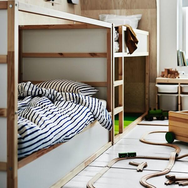 KURA säng står i ett barnrum med sängkäder på och leksaker runtomkring.