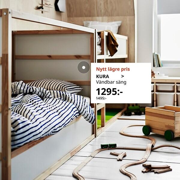 KURA säng syns i ett barnrum med randiga sängkläder och leksaker utspridda på golvet bredvid.
