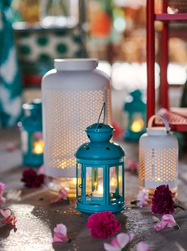 Kúsok neupravenej podlahy s lampášmi ROTERA a ÄDELHET, kvetmi a lupienkami rozhádzanými okolo.