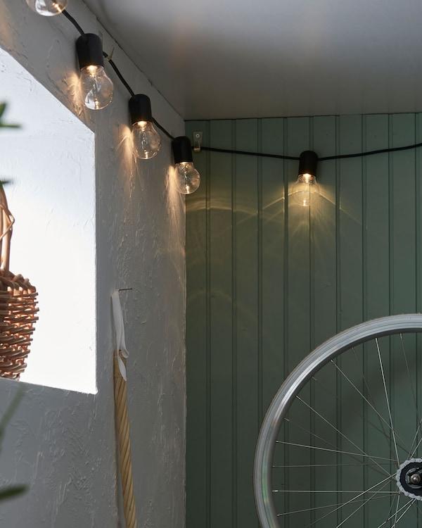 Kutak podruma ili garaže ukrašen rasvjetnim lancem obješenim na zidu u blizini stropa.