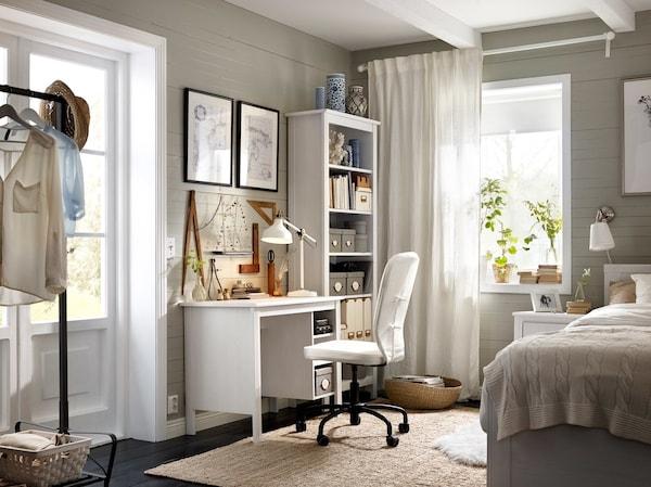 Kutak spavaće sobe s belim radnim stolom i visokom bibliotekom, uključujući BRUSALI radni sto i kancelarijsku stolicu bele navlake.