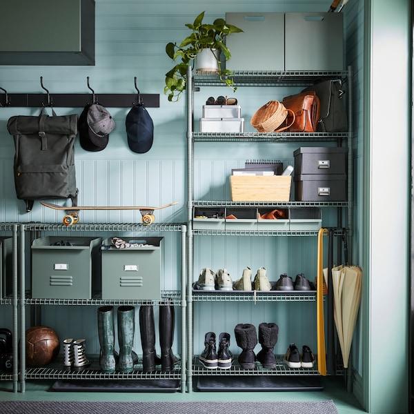 Kutije u sivim i zelenim nijansama, kao i sive kutije, biljka, cipele i tri vreće nalaze se na sistemu za odlaganje s otvorenim policama u sivim i zelenim nijansama.