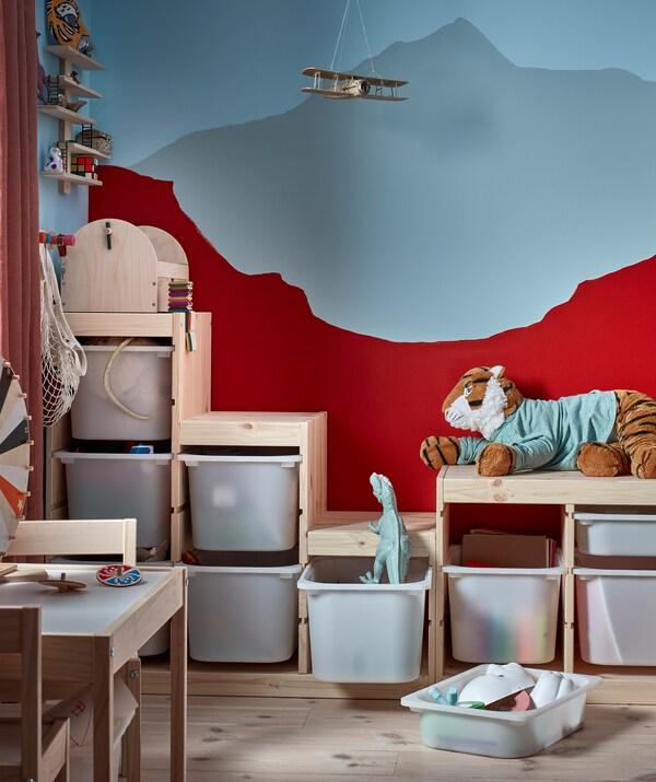 Куточок дитячої кімнати, де нерівномірний контур стелажів з іграшками відповідає зображенню на стіні.