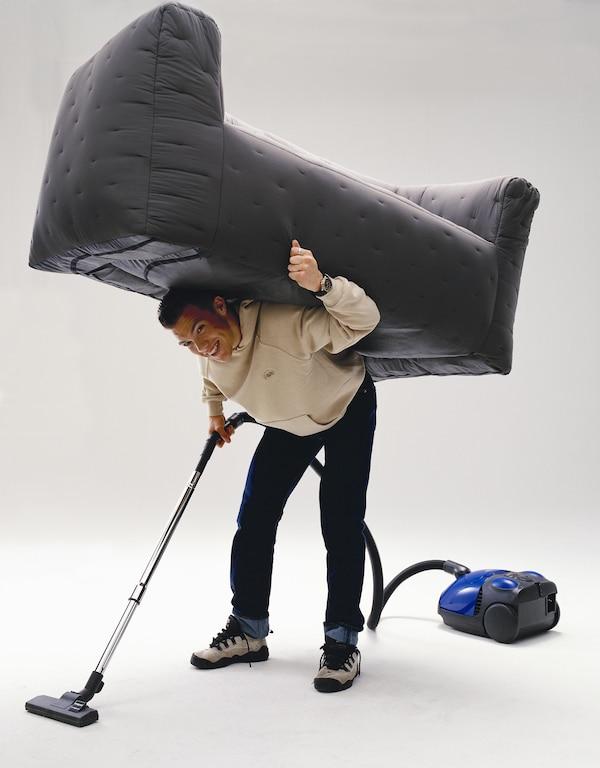 Kuva, jossa mies imuroi ilmalla täytettävän sohvan alta.