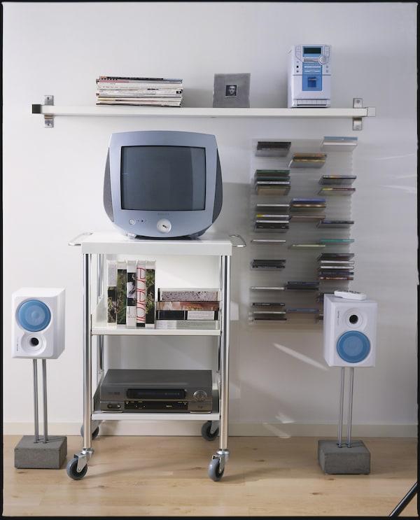 Kuva, jossa vanhanaikainen tv, vhs-nauhuri ja seinällä teline cd-levyille.