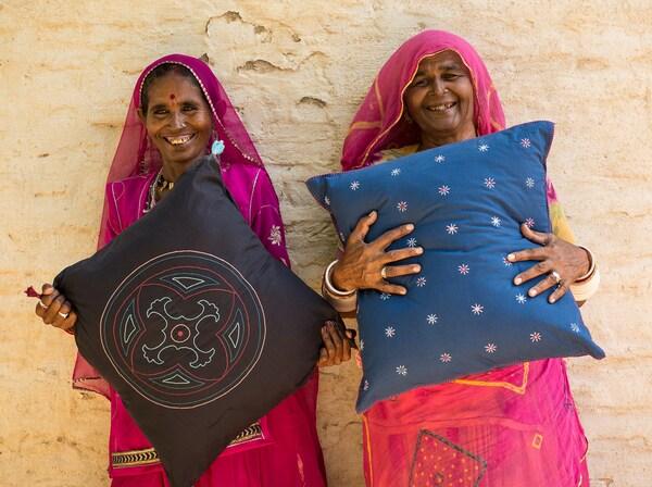 Kuvassa kaksi sosiaalista yrittäjää, jotka pitelevät käsityönä valmistettuja tyynyjä. Heille liiketoiminta on keino puuttua sosiaalisiin ja ympäristöön liittyviin haasteisiin, kuten köyhyyden vähentämiseen ja naisten vaikutusmahdollisuuksien lisäämiseen.