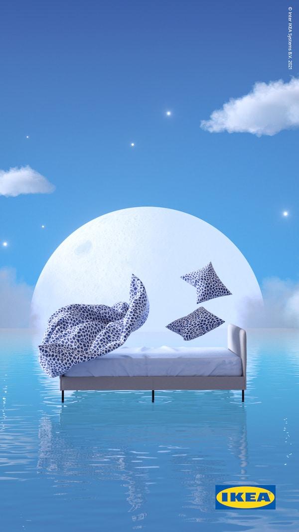 KVASTFIBBLA sengetøj i leopardmønstret i farverne hvid og blå løfter sig over en SLATTUM seng, der flyder oven på blåt vand foran en måne på vej op.
