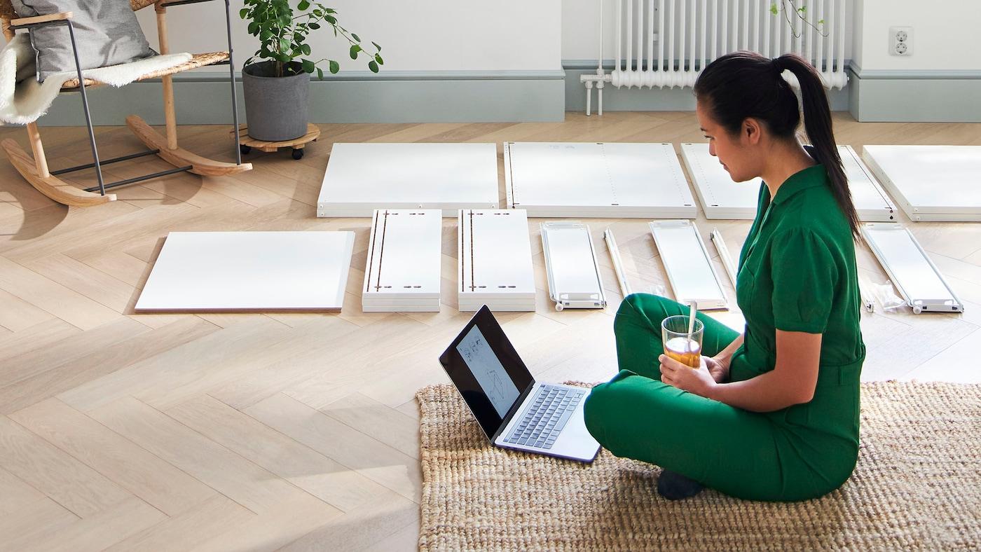 Kvinde sidder på gulvet ved en bærbar. Ved siden af hende ligger delene til et IKEA møbel.