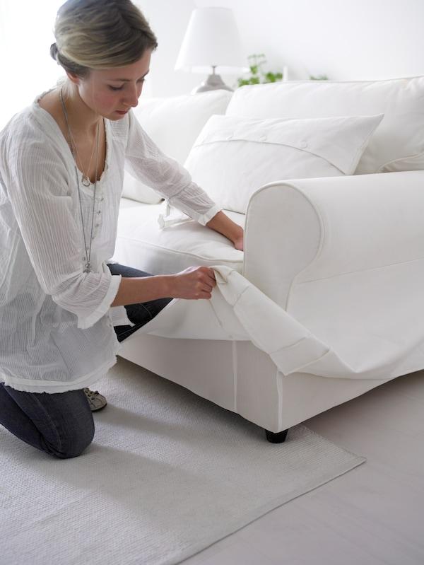 Kvinna som byter klädsel på en ETORP soffa.