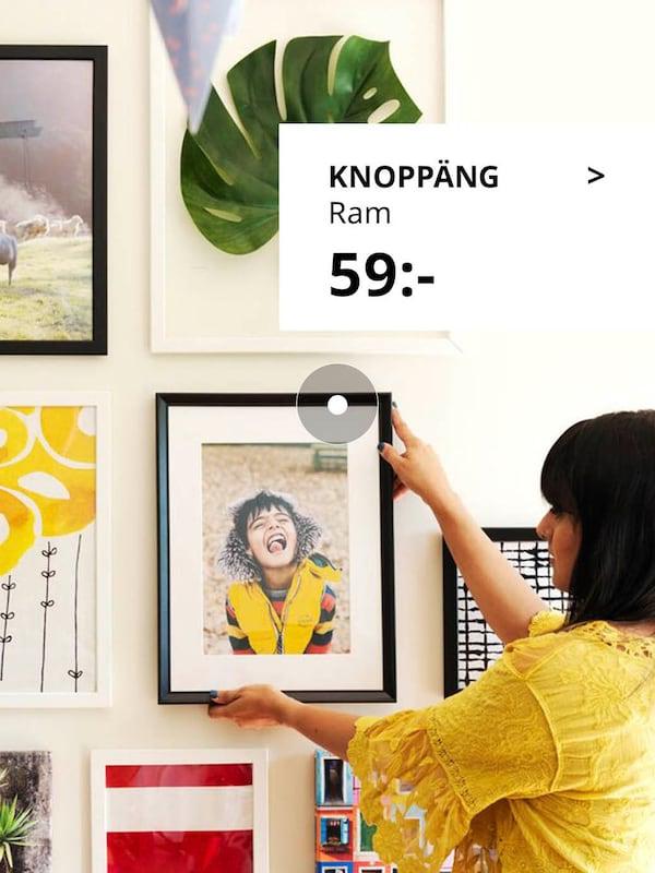 Kvinna som hänger upp tavlor.
