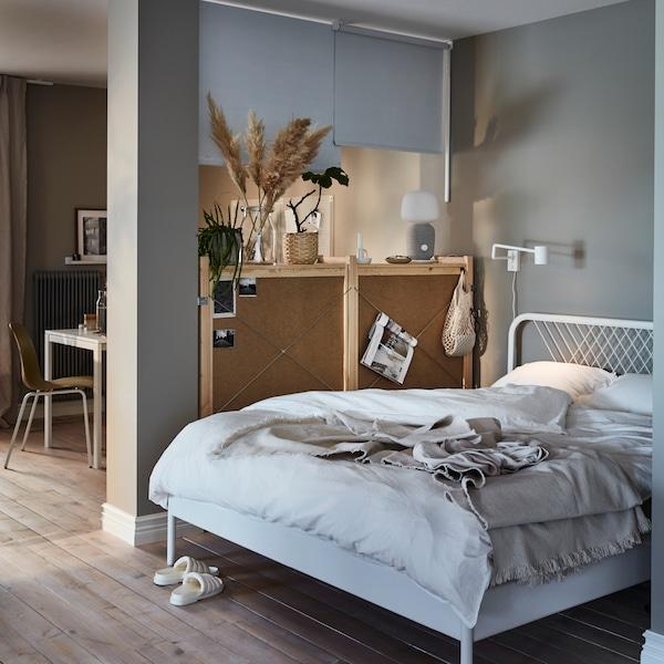 キャビネットと天井取り付け型ローラーブラインドを間仕切りとして、リビングルームに小さなスペースが作られています。スペースにはダブルベッドが置かれています。