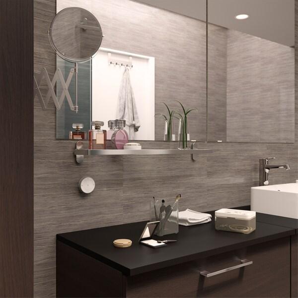 Kylpyhuone, jossa kätevä seinään kiinnitetty lasihylly niitä kauniita hajuvesipulloja varten.